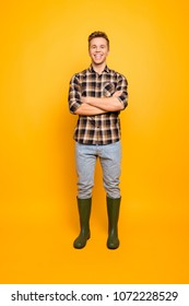 Vertical full-length portrait of cheerful friendly confident glad professional skilled gardener wearing brown shirt light blue jeans green rubber boots standing with folded arms isolated on background