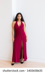 Vertical full-length portrait of gorgeous sultry hispanic young woman wearing elegant evening red dress with high slit and leaning against white wall