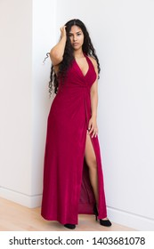 Vertical full-length portrait of gorgeous sultry hispanic young woman wearing elegant evening red dress with high slit and touching her long hair while leaning against white wall