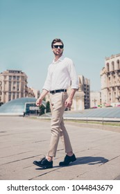 Vertical full-length portrait of serious handsome attractive virile masculine pensive foreigner wearing formal outfit white shirt beige pants walking in city center architecture houses background