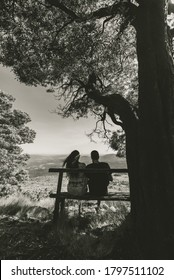 A vertical grayscale shot of a young loving couple sitting on a wooden bench under the tree