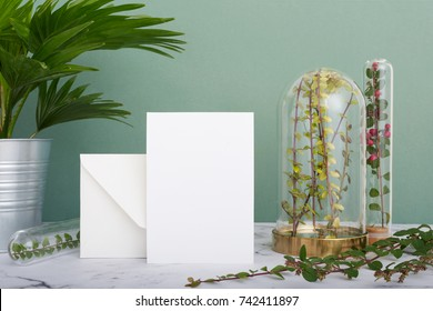 Vertical greeting card standing on table surrounded by plants