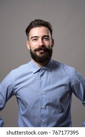 Vertical headshot of proud successful confident bearded businessman with arms on hips smiling at camera against gray studio background.