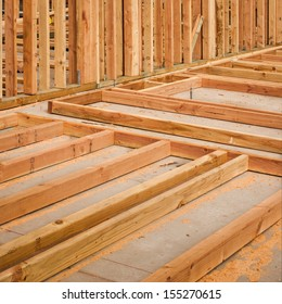 Vertical and horizontal boards on a concrete slab at a construction site.