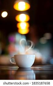 Vertikaler heißer Kaffee-Cup auf Holztisch auf unscharfem Hintergrund im Coffee Shop.