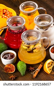 Vertical iimage of glass teapots set with colorful natural hot tea decorated with frruits and jam at wooden dark board background.