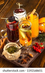 Vertical iimage of glasses set with different colorful natural hot tea decorated with autumn leaves and jam at wooden dark board background.