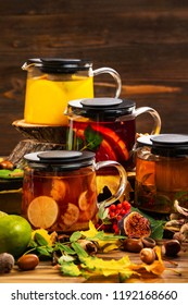 Vertical iimage of teapots set with different colorful natural tea decorated with autumn leaves at wooden dark board background.