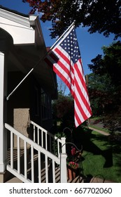 Vertical image of an American Flag mounted on the side of a house