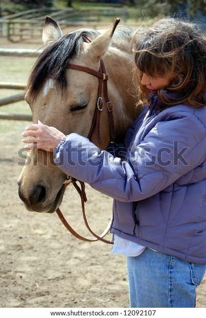Vertical image of a Baby Boomer era woman and her pretty dun horse.