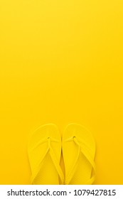 vertical image of beach flip-flops on the yellow background with copy space. summer concept