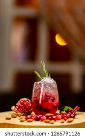 Vertical image of black currant cocktail with berries and frappe at decorated with pomegranate wooden table at evening window with moon and curtain background.