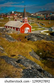Vertical image of the bright red Frelserens Kirke (Church of Our Saviour), Nuuk capital of Greenland on a Sunny day, rocks covered by green grass, no people and a bright blue sky, colourful cathedral