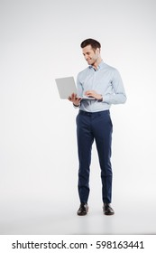 Vertical image of business man which holding and using laptop in studio. Isolated white background