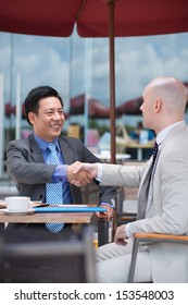 Vertical image of business partners handshaking at a cafe on the foreground