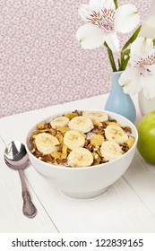 Vertical image of a cereal top with a banana slice with spoon and flower vase on the side