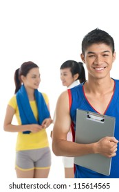 Vertical image of a cheerful fitness trainer and two female friends being ready for a workout