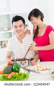 Vertical image of cheerful young cooks preparing meal