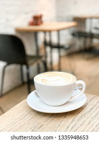 A vertical image (closeup) of a cappuccino in natural light with a short depth of field on the corner of a wooden table at a rustic cafe in the Chelsea neighborhood of London, England.