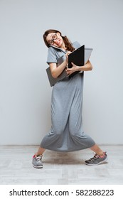 Vertical image of Clumsy Female nerd in eyeglassses which talking on phone and holding laptop, clipboard and notebook