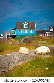 Vertical image of a colourful blue house in Nuuk, capital city of Greenland, Northern Europe, rocks covered by green grass in the foreground, no people, sunny day with bright blue sky summer sun
