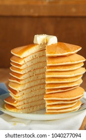 Vertical image of cut stack of pancake with honey and butter on top. Close up
