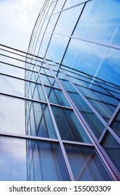 vertical image of facade of modern glass blue office and sky with clouds reflected