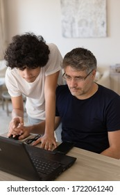 Vertical image of farther and son studying from home using black laptop, with farther sitting in front of the laptop and son standing behind his shoulder and pointing his finger on the screen