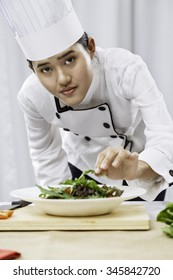 vertical image of female chef patiently placing salad on a plate