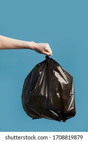 Vertical image of female hand holding black trash bag against blue background, waste sorting and recycling concept, copy space