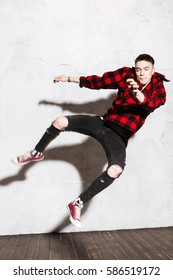 Vertical image of Hipster in shirt and jeans jumping in studio. Full length portrait