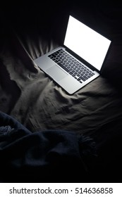 Vertical image of laptop in bed. Night working at home concept image with copyspace
