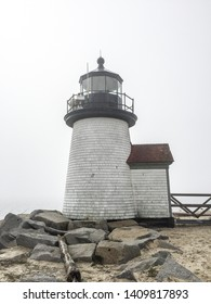 A vertical image of a lighthouse on an overcast day in Nantucket, Massachusetts.