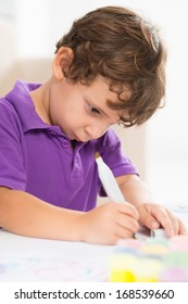 Vertical image of a little boy deeply concentrated at the drawing on the foreground