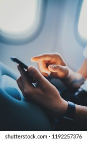 Vertical image of male hands using modern smartphone device in aircraft, businessman texting on touchscreen of cellphone checking email during flight, business travel