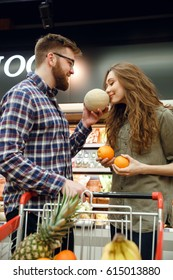 Vertical image of a man giving smell a melon to his woman in supermaket