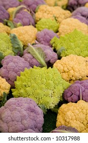 Vertical image of a mix of Romanesco broccoli, purple and orange cauliflower.