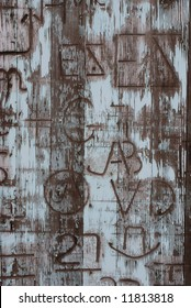 Vertical image of an old door covered in western branding iron marks