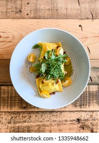 A vertical image from overhead of a beautifully plated dish of homemade ravioli with arugula, yellow tomatoes and guanciale centered on a rustic, wooden table.