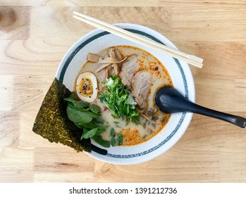 A vertical image from overhead of a beautifully presented bowl of Tonkotsu ramen with cha shu (pork belly), egg, bamboo, sprouts, spinach, mushrooms and nori centered on a rustic, wooden table.