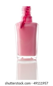 Vertical image of pink nail polish running out of a container on a reflective surface