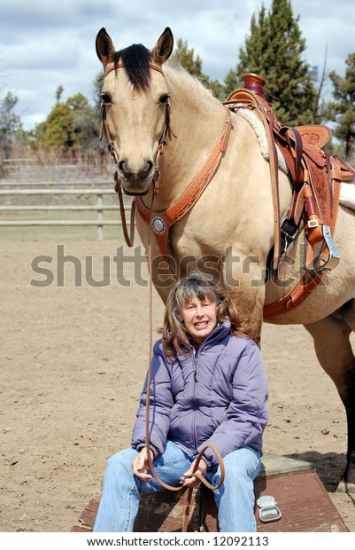 Vertical image of a pretty dun quarter horse standing on a circus platform while her owner sits at her feet, smiling into the camera.