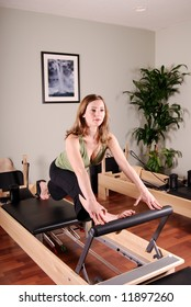 Vertical image of a professional Pilates instructor excercising on a Reformer.
