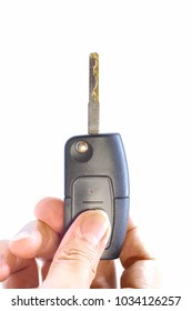 Vertical image of right hand of male holding modern remote car key and thumb is pressing on lock button isolated on white background