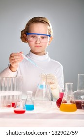 Vertical image of a school child mixing substances to observe reactions