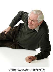 A vertical image of a senior man on the ground who has injured his hip in a fall.  Isolated on white.