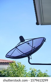 Vertical image of silhouette black satellite dish hanging on house wall with little birds perching on the iron dish against clear blue sky