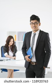 Vertical image of a smiling office working holding a touchpad, his pretty colleague working in the background