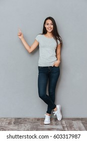 Vertical image of smiling woman ponting away and looking at camera while holding arm in pocket and posing in studio over gray background