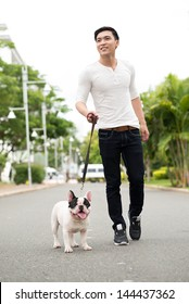 Vertical image of a smiling young man walking his pet